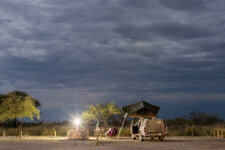 ETOSHA, NAMIBIA - APRIL 9, 2017: Car camp at night bright light from moon in Okaukuejo Rest Camp. Okaukuejo is located 17 km from the southern entrance of the Etosha park, and famous for its flood-lit waterhole