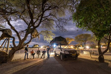 ETOSHA, NAMIBIA - APRIL 9, 2017: Traveler group portrait in Okaukuejo Rest Camp. Okaukuejo is located 17 km from the southern entrance of the Etosha park, and famous for its flood-lit waterhole Editöryel