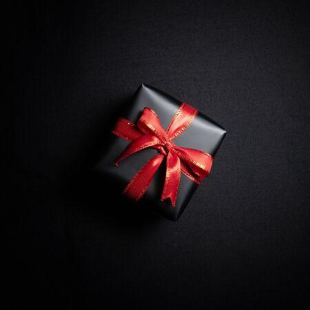 Vista dall'alto della confezione regalo nera con nastri rossi isolati su sfondo nero. Giorno di Santo Stefano di concetto di acquisto e composizione di vendita del Black Friday. Archivio Fotografico