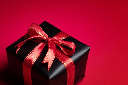 Top view of black christmas gift box with red and black ribbons isolated on red background. Shopping concept christmas day, valentin's day and black Friday sale composition. Stock Photo - 134276453