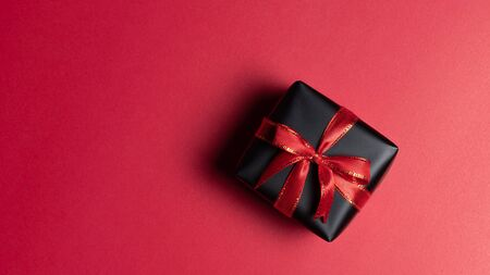 Top view of black christmas gift box with red and black ribbons isolated on red background. Shopping concept christmas day, valentin's day and black Friday sale composition. Stock Photo - 134276454