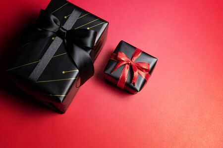 Top view of black christmas gift box with red and black ribbons isolated on red background. Shopping concept christmas day, valentin's day and black Friday sale composition. Stock Photo - 134276456