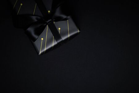 Top view of black gift box with black ribbons isolated on black background. Shopping concept boxing day and black Friday sale composition. Stock Photo - 134276457
