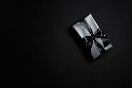 Top view of black gift box with black ribbons isolated on black background. Shopping concept boxing day and black Friday sale composition. Stock Photo - 134276461