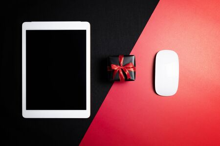 Cyber Monday Sale free space for text with mouse, laptop, tablet and gift box on red and black background. Shopping Online concept and Cyber Monday composition. Stock Photo - 134276462