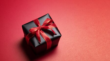 Top view of black christmas gift box with red and black ribbons isolated on red background. Shopping concept christmas day, valentin's day and black Friday sale composition. Stock Photo - 134276471