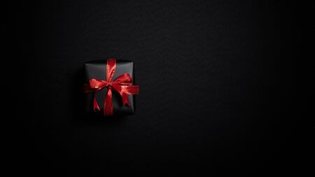 Top view of black gift box with red ribbons isolated on black background. Shopping concept boxing day and black Friday sale composition. Stock Photo - 134276472