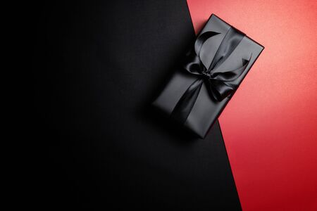 Top view of black gift box with black ribbons isolated on red and black background. Shopping concept boxing day and black Friday sale composition. Stock Photo - 134276474
