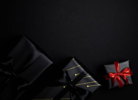 Top view of black gift box with red and black ribbons isolated on black background. Shopping concept boxing day and black Friday sale composition. Stock Photo - 134276476