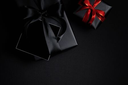 Top view of free space card for text with black gift box isolated on black background. Shopping concept boxing day and black Friday composition. Stock Photo - 134276480