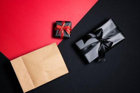 Top view of gift box with red, shopping paper bag, black ribbons and piggy bank isolated on red and black background. Shopping concept boxing day and black Friday sale composition. Stock Photo