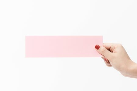 Close up women holding pink blank paper on white background. Free space, ready for type with text banner.