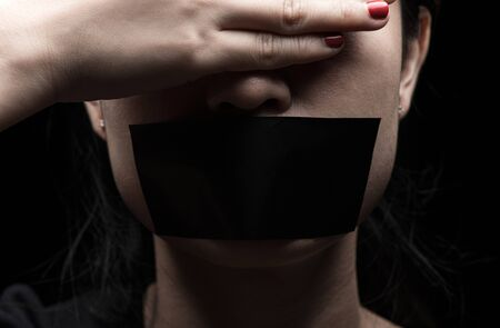 Concept on the topic of freedom of speech, censorship, freedom of press. International Human Right day: the girl's face is sealed her mouth with black paper