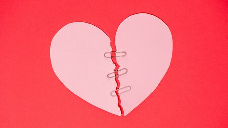 Red paper heart torn in half secured with safety clip on red background Stock Photo - 139312892