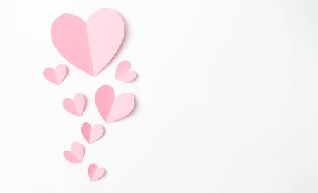 Paper elements in shape of heart flying on white paper background. Love and Valentine's day concept. Birthday greeting card design. Stock Photo - 139312801