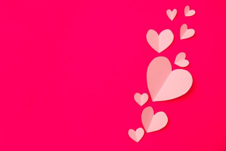 Paper elements in shape of heart flying on pink paper background. Love and Valentine's day concept. Birthday greeting card design. Stock Photo - 139313067