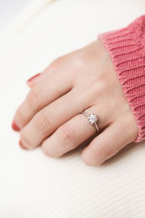 Close up of an elegant engagement diamond ring on woman finger with pink sweater winter clothe. love, wedding and Valentine's day concept. 免版税图像