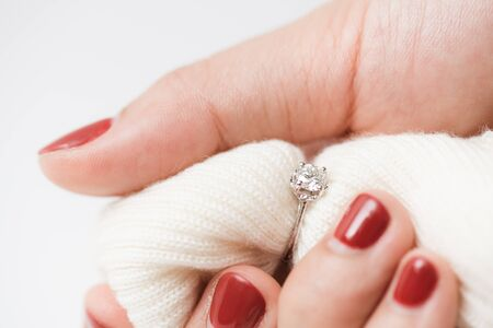 Close up of an elegant engagement diamond ring on woman finger with pink sweater winter clothe. love, wedding and Valentine's day concept. Stock Photo - 139313020