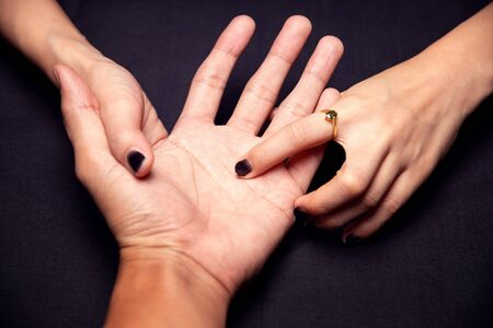 Fortune teller reading fortune lines on hand, top view - Palmistry concept. Stock Photo - 139572050