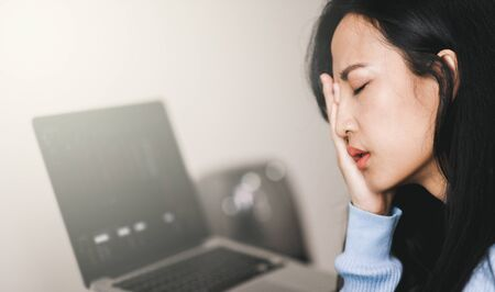 An asian woman getting anxiety and depression after checking news about global pandemic. Lockdown mental health. Coronavirus outbreak