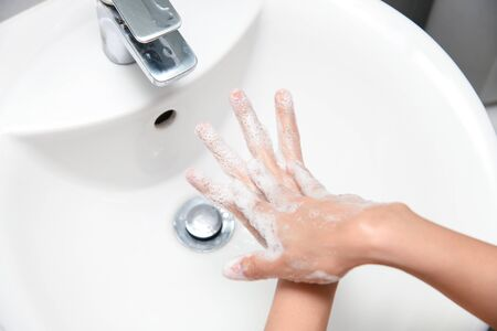 Woman use soap and washing hands under the water tap. Hygiene concept hand detail.