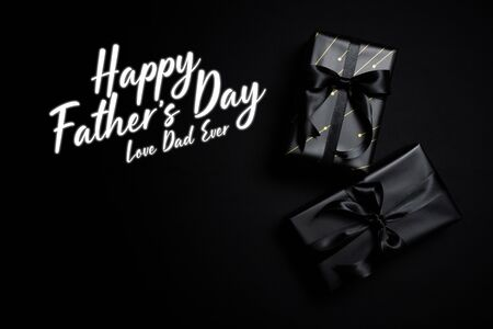 Happy Father's Day background concept with top view of black gift box with black ribbons isolated on black background.