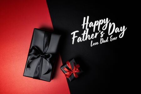 Happy Father's Day background concept with top view of black gift box with red and black ribbons isolated on black and red background. Stock Photo