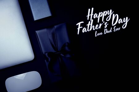 Happy Father's Day background concept with mouse, laptop, hard dirve and gift box on black background.