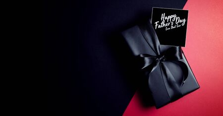 Happy Father's Day background concept with top view of black gift box with ribbons isolated on dark theme background. Stock Photo