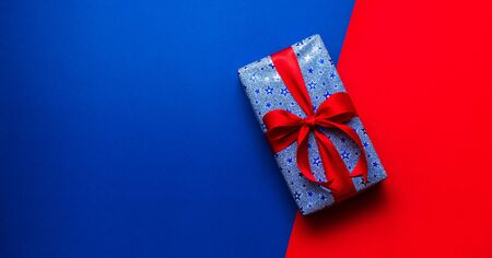 gift box with red ribbon in red and blue background