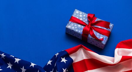 gift box with red ribbon and american flag in blue background