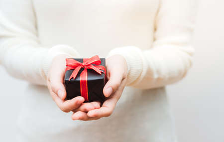 Close up shot of female hands holding a small gift wrapped with gold ribbon. Shallow depth of field with focus on the little box. Stock Photo