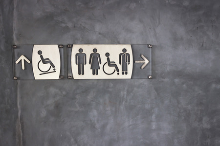 exposed: Toilet sign and direction on exposed concrete wall background Stock Photo