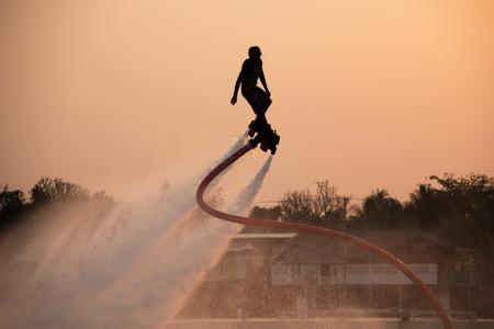 volar: El nuevo deporte espectacular, la silueta de un hombre que muestra el Flyboard en el río de Tailandia Foto de archivo