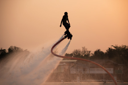 fly: The new spectacular sport,Silhouette of a man showing the flyboard in the river of Thailand