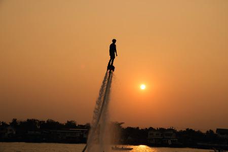 moto acuatica: El nuevo deporte espectacular, la silueta de un hombre que muestra el Flyboard en el río de Tailandia Foto de archivo