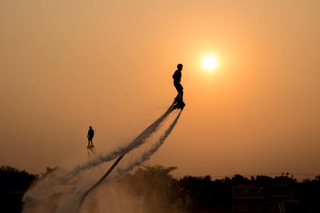 새로운 장관 스포츠, 태국의 강에서 비행 보드를 보여주는 두 남자의 실루엣 스톡 콘텐츠