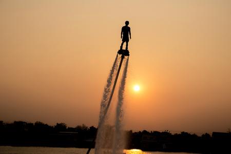 moto acuatica: El nuevo deporte espectacular, la silueta de un hombre que muestra la placa de mosca en el río de Tailandia