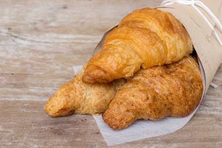 lubricate: Fresh croissants in a paper wrap on wooden background