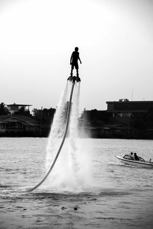 volar: El nuevo deporte espectacular, la silueta de un hombre que muestra la placa de mosca en el r�o de Tailandia