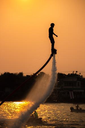 volar: El nuevo deporte espectacular, la silueta de un hombre que muestra la placa de mosca en el río de Tailandia
