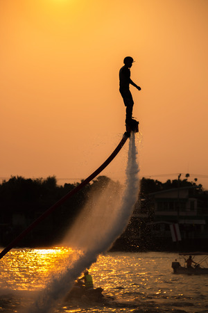 fly: The new spectacular sport,Silhouette of a man showing the fly board in the river of Thailand Stock Photo