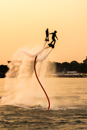 fly: The new spectacular sport,Silhouette of two man showing the fly board in the river of Thailand