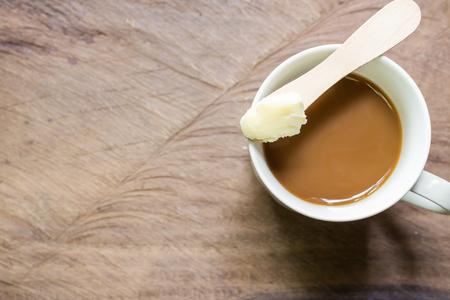 aceite de coco: Café mezclado con el probador de mantequilla bien. Nueva tendencia puede cambiar para siempre la forma de beber café. En lugar de la crema y el azúcar de costumbre, en el fondo de madera con espacio de copia