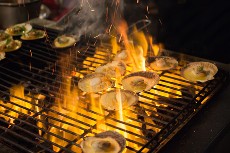 gridiron: Grilled scallops topped with butter, garlic and parsley on a gridiron over fire at the seafood night market