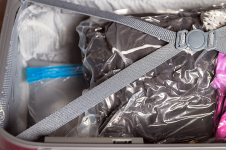 Crossed belts on vacuum compress bag for clothes and expanded your space suitcase.