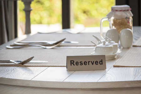 Reserved sign on a table in restaurant by the window.