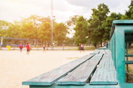Green old wooden seat sport, stand cheer and active young volleyball players at the sand outdoor court with tree background (selective focus) Standard-Bild
