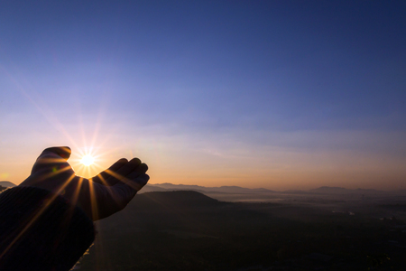 Sun on hand; Silhouette of female hand holding sun rays with mountain in sunrise scene (copy space for text)