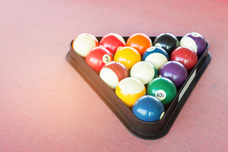 Billiards pool game. Red cloth table with colorful balls.